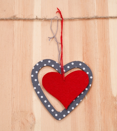 heart shaped stuff: two hearts hung up on the string on wooden background