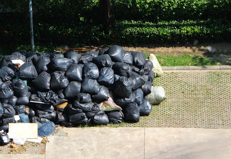 Garbage in a black bag waiting for service garbage truck. Big trash bags ready for transportation. Stock Photo