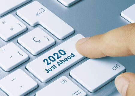 2020 Just Ahead Written on White Key of Metallic Keyboard. Finger pressing key