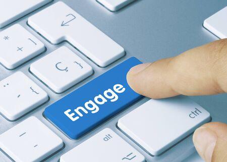Engage Written on Blue Key of Metallic Keyboard. Finger pressing key