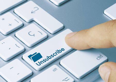Afmelden geschreven op blauwe toets van metalen toetsenbord. Vinger indrukken van toets