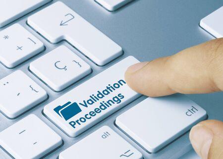 Validation Proceedings Written on Blue Key of Metallic Keyboard. Finger pressing key.