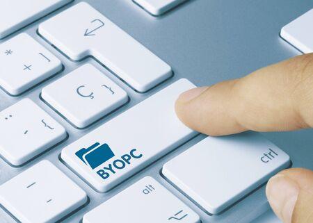 BYOPC Written on White Key of Metallic Keyboard. Finger pressing key.