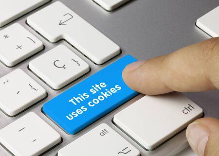 This site uses cookies Written on White Key of Metallic Keyboard. Finger pressing key. Stockfoto
