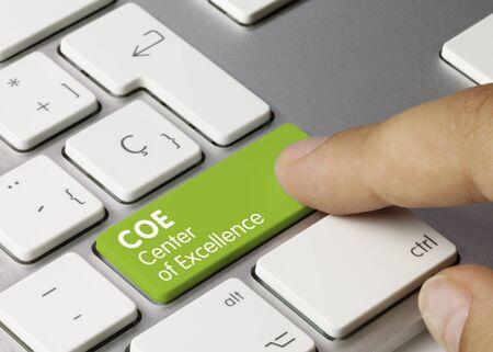 COE Center of Excellence Geschrieben auf der grünen Taste der Metallic-Tastatur. Finger drücken Taste. Standard-Bild