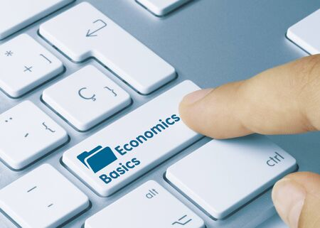 Economics Basics Written on White Key of Metallic Keyboard. Finger pressing key.