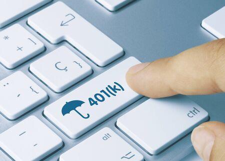 401(k) Written on Blue Key of Metallic Keyboard. Finger pressing key Stock Photo