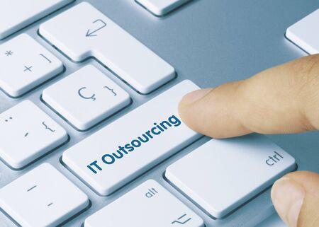 IT Outsourcing Written on White Key of Metallic Keyboard. Finger pressing key.