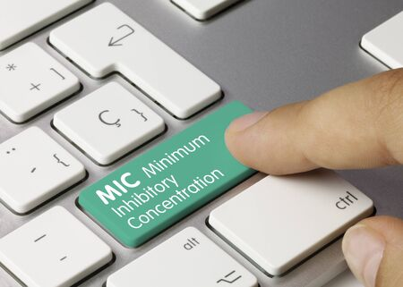 MIC Minimum Inhibitory Concentration Written on Green Key of Metallic Keyboard. Finger pressing key.