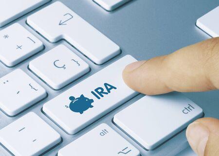 IRA Written on White Key of Metallic Keyboard. Finger pressing key.