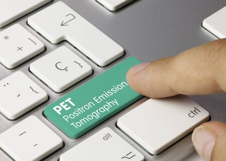 PET Positron Emission Tomography Written on Green Key of Metallic Keyboard. Finger pressing key. Zdjęcie Seryjne