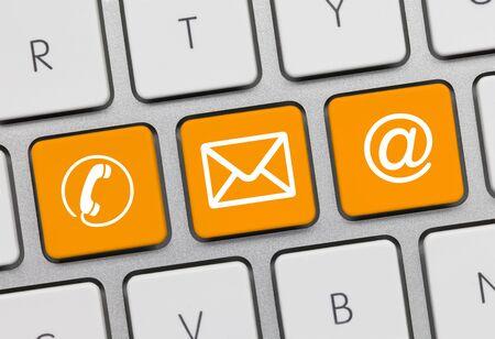Contacto Escrito en la llave anaranjada del teclado metálico. Tecla presionando el dedo