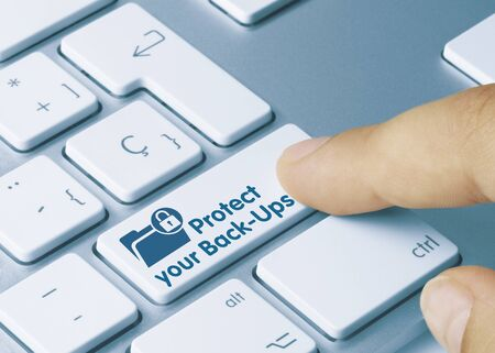 Protect your Back-Ups Written on Blue Key of Metallic Keyboard. Finger pressing key.