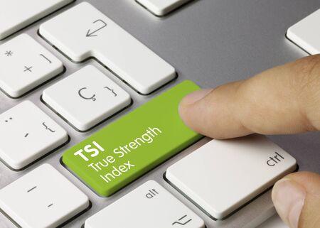 TSI True Strength Index Written on Green Key of Metallic Keyboard. Finger pressing key.