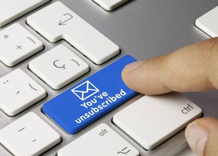 Je hebt je uitgeschreven Geschreven op de blauwe toets van het metalen toetsenbord. Vinger drukken op de toets. Stockfoto