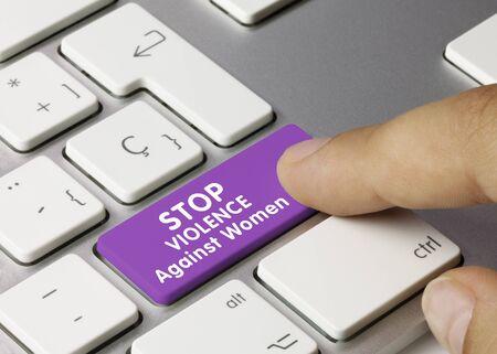 STOP Violence Against Women Written on Violet Key of Metallic Keyboard. Finger pressing key.