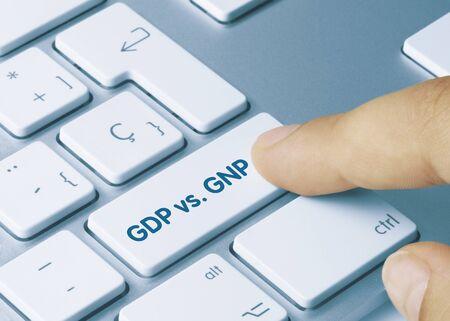 GDP vs GNP Written on Blue Key of Metallic Keyboard. Finger pressing key.