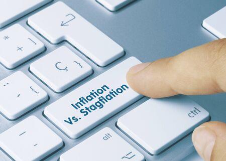 Inflation vs. Stagflation Written on Blue Key of Metallic Keyboard. Finger pressing key. Banco de Imagens