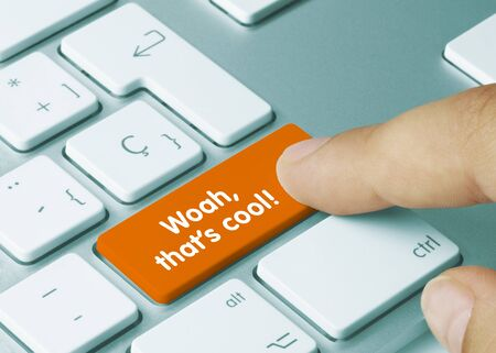 Woah, that's cool! Written on Orange Key of Metallic Keyboard. Finger pressing key. Standard-Bild