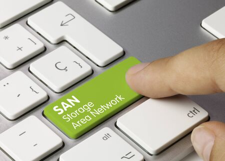 SAN Storage Area Network Written on Green Key of Metallic Keyboard. Finger pressing key.