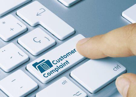 Customer Complaint Written on Blue Key of Metallic Keyboard. Finger pressing key.