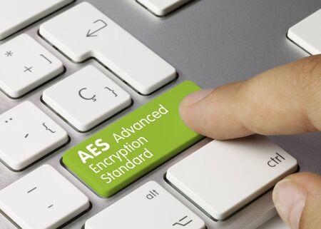 AES Advanced Encryption Standard Written on Green Key of Metallic Keyboard. Finger pressing key.