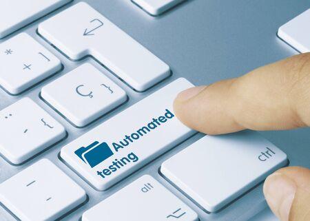 Automated testing Written on Blue Key of Metallic Keyboard. Finger pressing key. Imagens