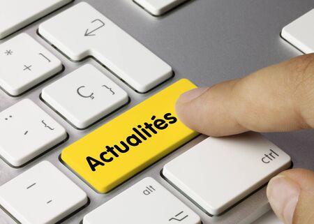 Actualités Written on Yellow Key of Metallic Keyboard. Finger pressing key. Stock fotó