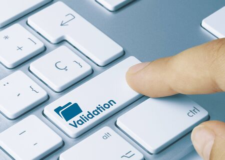 Validation Written on Blue Key of Metallic Keyboard. Finger pressing key. Imagens