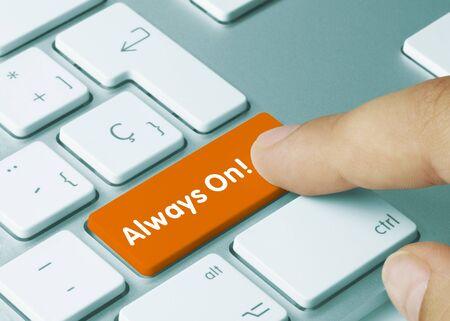 Always On! Written on Orange Key of Metallic Keyboard. Finger pressing key. Stock Photo