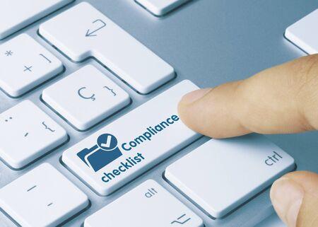Compliance checklist Written on Blue Key of Metallic Keyboard. Finger pressing key. Banque d'images