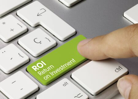 ROI Return on Investment Written on Green Key of Metallic Keyboard. Finger pressing key.