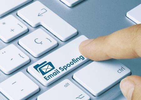 Email Spoofing Written on Blue Key of Metallic Keyboard. Finger pressing key. Imagens
