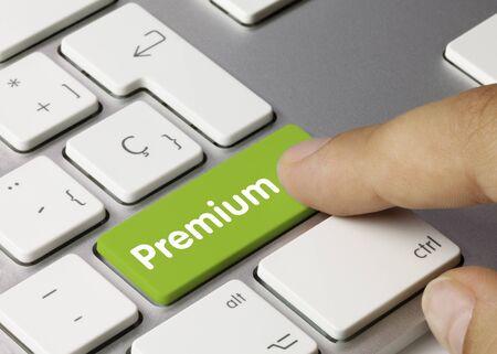 Premium Written on Green Key of Metallic Keyboard. Finger pressing key. Stock Photo