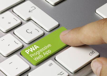 PWA progressive web app Written on Green Key of Metallic Keyboard. Finger pressing key.