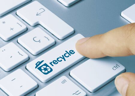 recycle Written on Blue Key of Metallic Keyboard. Finger pressing key.