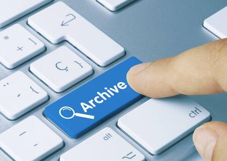 Archive Written on Blue Key of Metallic Keyboard. Finger pressing key. Standard-Bild