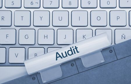 Audit Written on Blue Key of Metallic Keyboard. Finger pressing key.