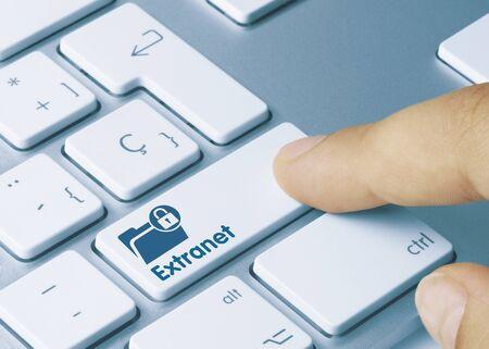 Extranet Written on Blue Key of Metallic Keyboard. Finger pressing key.