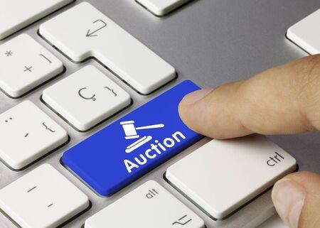Auction Written on Blue Key of Metallic Keyboard. Finger pressing key.
