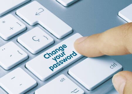 Change your password Written on Blue Key of Metallic Keyboard. Finger pressing key.