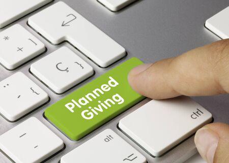 Planned Giving Written on Green Key of Metallic Keyboard. Finger pressing key.