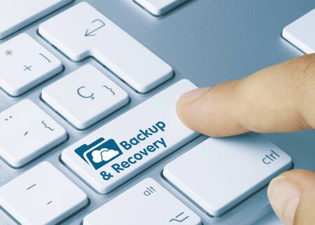 Backup & Recovery Written on Blue Key of Metallic Keyboard. Finger pressing key.