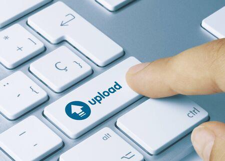 Upload Written on Blue Key of Metallic Keyboard. Finger pressing key.