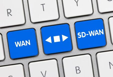 WAN versus SD-WAN Written on Blue Key of Metallic Keyboard. Finger pressing key.