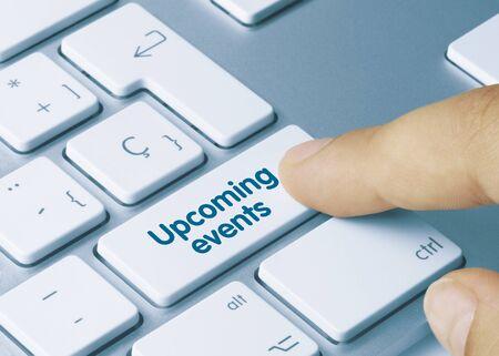 Upcoming events Written on Blue Key of Metallic Keyboard. Finger pressing key.