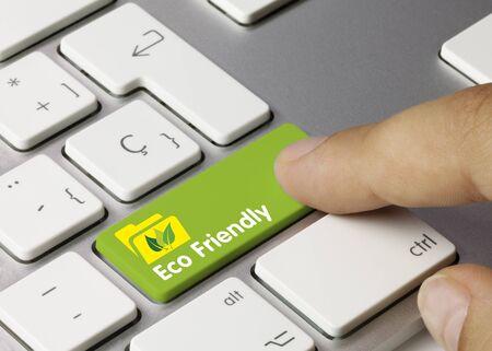 Eco Friendly Written on Green Key of Metallic Keyboard. Finger pressing key. Stock Photo