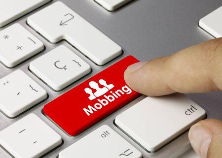 Mobbing Written on Red Key of Metallic Keyboard. Finger pressing key.