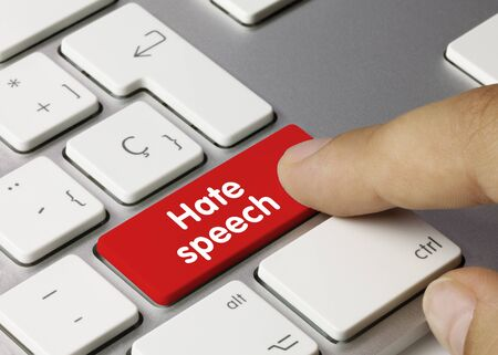 Hate speech Written on Red Key of Metallic Keyboard. Finger pressing key.