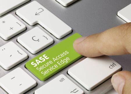 SASE Secure Access Service Edge Written on Green Key of Metallic Keyboard. Finger pressing key.